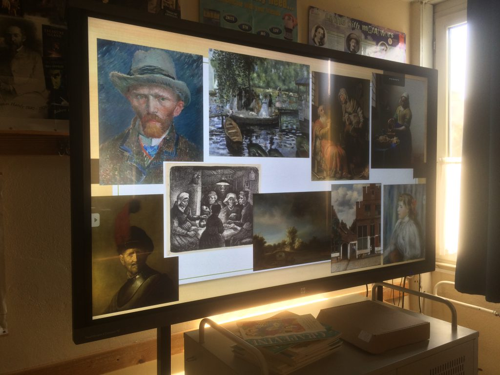 teh power of arts - students discovering and discribing a display of paintings on a board
