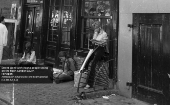 European History:Street scene with young people sitting on the floor