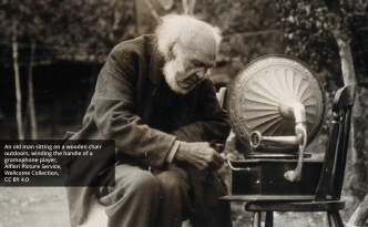 An old man sitting on a wooden chair outdoors, winding the handle of a gramophone player